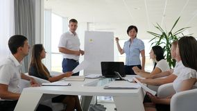 Colleagues giving presentation near flipchart for partners at meeting. In white and spacious office stock footage