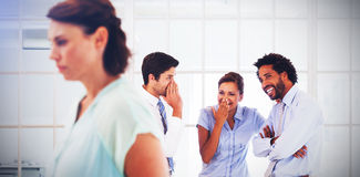 Colleagues gossiping with sad businesswoman in foreground. Colleagues gossiping with sad young businesswoman in foreground at a bright office Stock Image
