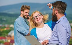 Colleagues happy with laptop work outdoor sunny day, nature background. Business partners meeting non formal atmosphere. Mobile internet concept. Colleagues royalty free stock photos