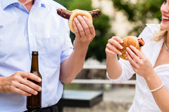Colleagues having sausages and beer after work Royalty Free Stock Images