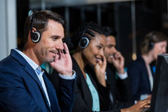 Colleagues with headsets using computer at office Stock Photo