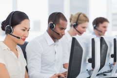 Colleagues with headsets using computers at office Royalty Free Stock Photo