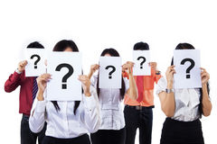 Colleagues holding question mark signs. In front of their faces, isolated on white Royalty Free Stock Photos