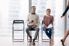 Colleagues or job applicants gazing at female coworker, fake fri. Confident businesswoman walking by male and female job candidates sitting on chairs, following Stock Photography