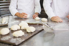 Colleagues kneading uncooked dough on worktop Stock Photography