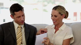 Colleagues laughing together while working on a notepad. Sat on a sofa stock footage