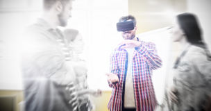 Colleagues looking at businessman wearing virtual reality headset. In creative office Stock Image