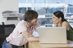 Colleagues Looking At Each Other BY Laptop At Desk Royalty Free Stock Photo