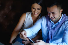 Colleagues looking at the mobile phone and laughing Royalty Free Stock Photos