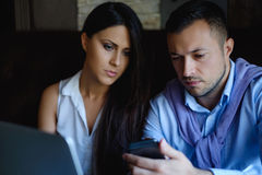 Colleagues looking at mobile phone seriously Stock Image