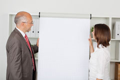 Colleagues looking on white flipchart Royalty Free Stock Photos