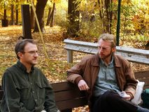 Colleagues on lunch break. Two coworkers taking lunch break in a park with autumn colors royalty free stock image
