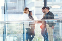 Colleagues meet in the hallway office building, shake hands royalty free stock photos
