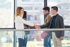 Colleagues meet in the hallway office building, shake hands stock image