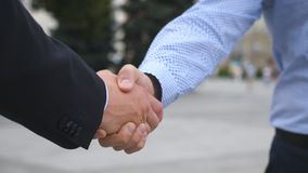 Colleagues meet and shake hands in the city background. Two businessmen greeting each other in urban environment. Business handshake outdoor. Shaking of male stock video