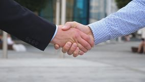 Colleagues meet and shake hands in the city background. Two businessmen greeting each other in urban environment royalty free stock photo