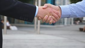 Colleagues meet and shake hands in the city background. Two businessmen greeting each other in urban environment. Business handshake outdoor. Shaking of male stock footage