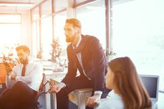 Colleagues at meeting in sunny office. CEO Sitting On Desk In Sunny Office. Colleagues Sitting On Chairs Nearby. Creating Project Ideas. Business Concept royalty free stock image