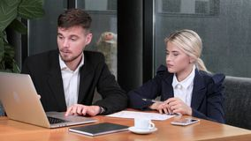 Colleagues met in rainy weather at the cozy cafe. Two young fellow man and woman, laptop on a table, a mobile phone, business papers, dressed in business suits stock footage