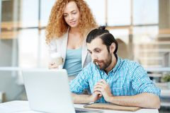 Colleagues networking. Pensive designer or engineer with pencil by his mouth and his colleague with drink looking at laptop display and reading online data stock photos