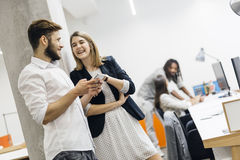 Colleagues in office using phones and smiling Royalty Free Stock Image