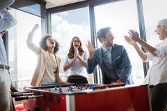 Colleagues playing table football in the break. Colleagues playing table football in the break in office stock photo