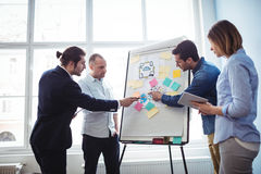 Colleagues pointing on white board. In meeting room at creative office Stock Photos