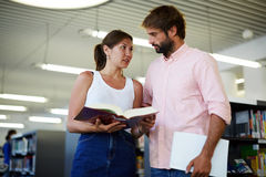 Colleagues preparing for a new project, a girl holding a thick reference book. Portrait of young couple of students looking at each other while standing in the Stock Images