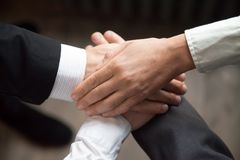 Colleagues putting hands together motivating for better results royalty free stock images