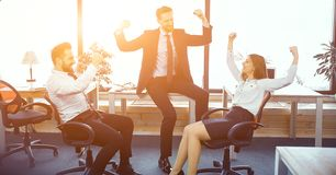 Fun moments in sunny modern office. Colleagues Raised Their Hands To Express Success And Victory In Sunny Modern Office. Business Concept royalty free stock images