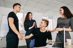 Colleagues shaking hands and applauding stock images