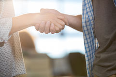 Colleagues shaking hands in creative office Stock Images