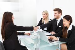 Colleagues shaking hands at desk Stock Photos