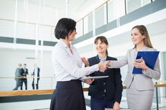 Colleagues Shaking Hands While Standing In Office stock photography