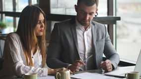 Colleagues sign a contract sitting in a restaurant for lunch. Young businessman and businesswoman working with documents sitting at the desk, colleagues stock video footage