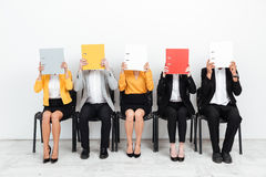 Colleagues sitting in office covering faces with folders. Royalty Free Stock Photos