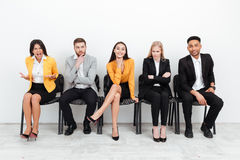 Colleagues sitting in office near screaming woman. Photo of a group of young colleagues sitting in office near screaming women looking at camera Stock Photos