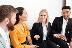 Colleagues sitting in office talking with each other. Royalty Free Stock Photo