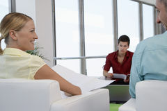 Colleagues Smiling At Eachother In Waiting Room Royalty Free Stock Photography
