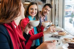 Colleagues smiling while eating delicious cakes during break in a coffee shop. Side view of three young colleagues smiling happy while eating delicious cakes stock images