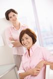 Colleagues smiling in office. Portrait of female colleagues in office, smiling at camera stock photography