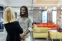 Colleagues smiling and talking. In a beautifully designed office stock images