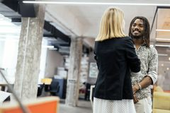 Colleagues smiling and talking. In a beautifully designed office royalty free stock photo