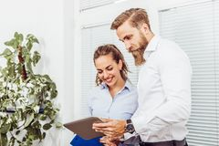 Colleagues stading in office using digital tablet stock images