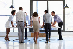 Colleagues standing around a conference table Royalty Free Stock Images