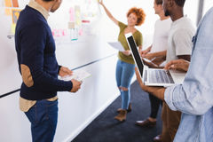 Colleagues standing by businesswoman explaining plan on whiteboard Royalty Free Stock Photo