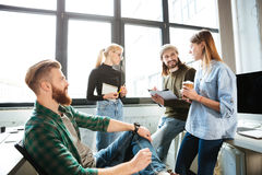 Colleagues standing in office and talking with each other. Image of young colleagues standing in office and talking with each other. Looking aside Stock Images