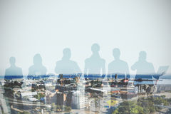 Composite image of colleagues standing over white background. Colleagues standing over white background against high angle view of roads in city Royalty Free Stock Image