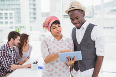 Colleagues standing and using tablet together Stock Image