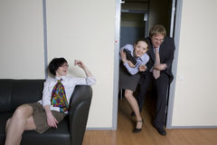 Colleagues struggle in doors for chance be first Royalty Free Stock Photos